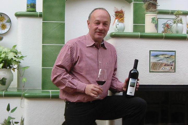 Herbert Schilling präsentiert den Rotwein Camilla im Wintergarten vor dem Kachelofen